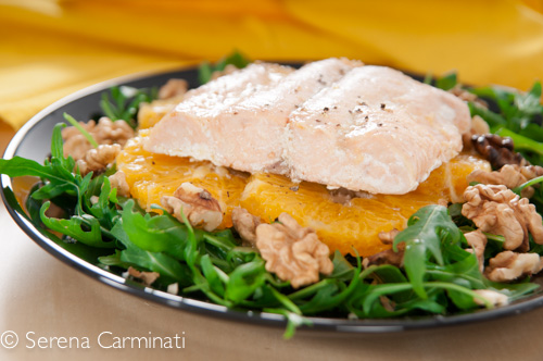 Steamed salmon with rocket and oranges (front view, close up)