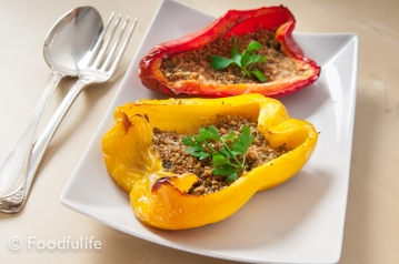 one red and one yellow stuffed, oven baked, peppers, on a rectangular dish with tablespoon and fork on the side