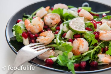 prawn and pomegranate salad with rocket a slice of lime on top, on a black ceramic dish with a fork