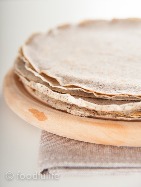 pile of crepes on round wooden cutting table on beige table mat