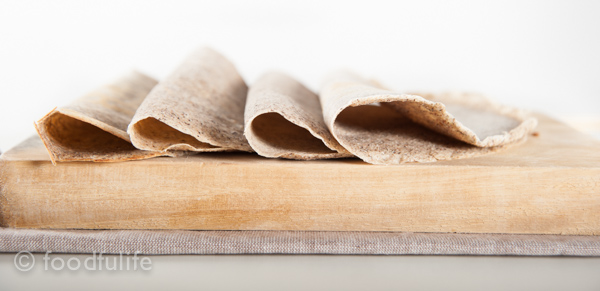 crepes on rectangular cutting board on a beige cutting mat, with white background