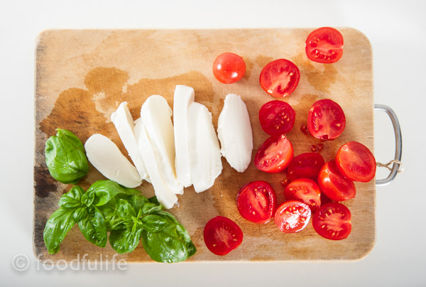 Mozzarella cheese, cherry tomatoes and basil leaves on wooden board.