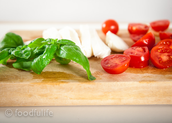 basil leaves, mozzarella and cherry tomatoes on a wooden board.