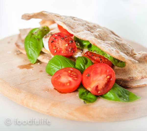 Italian flatbread with Caprese salad on a wooden board. Piadina con mozzarella e pomodorini.