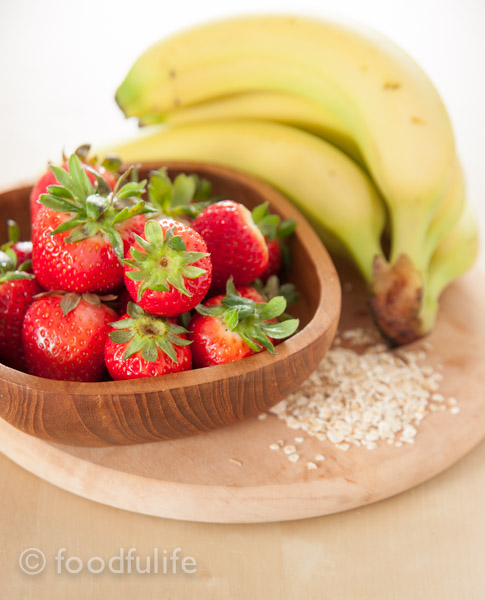Strawberry and banana smoothy in a glass jar on green napkin, on a wood board, frullato di fragole e banana