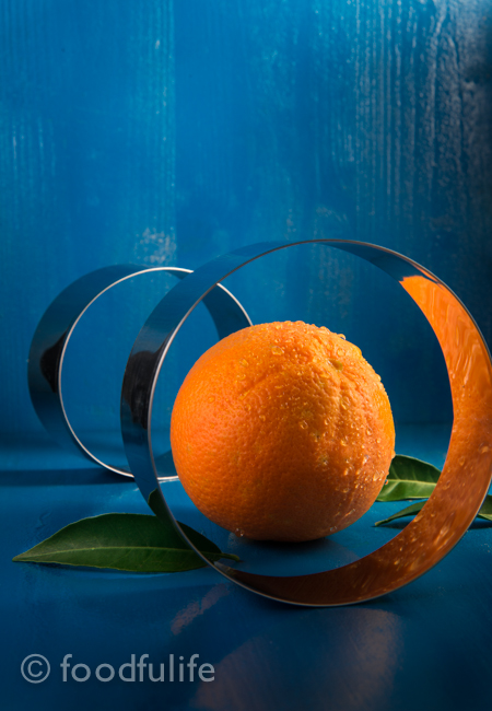 Orange with pastry cutters on blue background