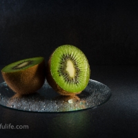 Kiwi Fruit On Round Mirror With Droplets