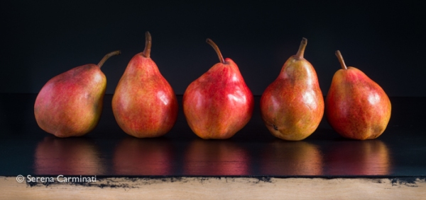 Red pears on black background