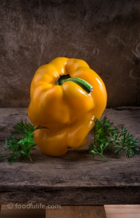 Yellow bell pepper with carrot leaves