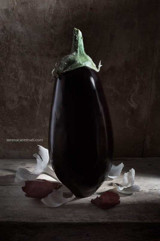 Aubergine with garlic and onion skin on wood